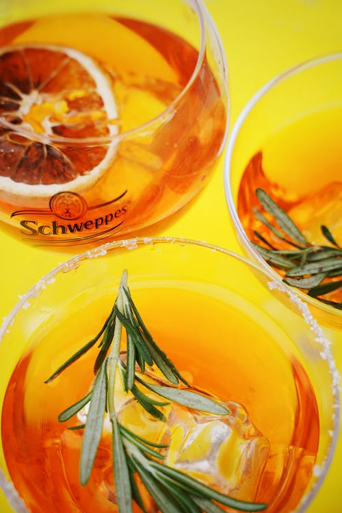 Two Clear Drinking Glasses With Orange Liquid