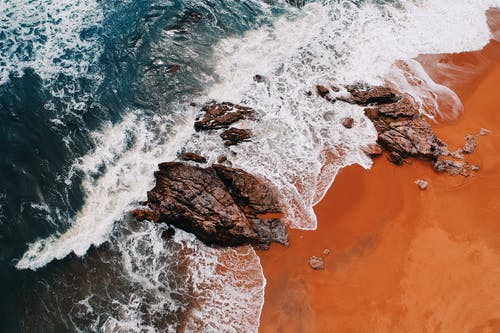 Brown Rocky Shore With Water Waves