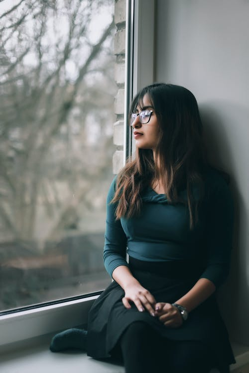 Tender casual brunette in glasses sitting in solitude on windowsill looking away in thoughts