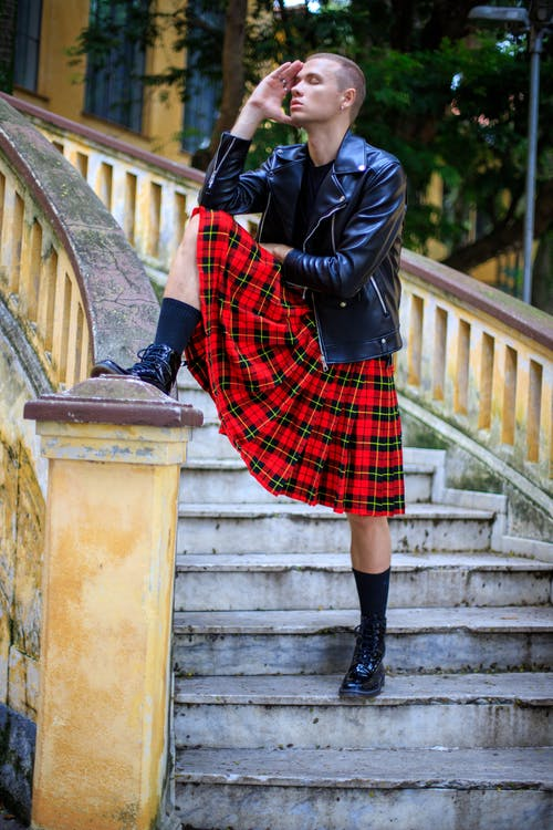 Full body sensual male model in leather jacket and red tartan kilt standing on aged stairs