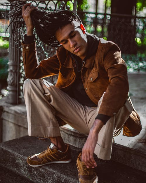 Stylish young African American man in sneakers and trendy jacket holding long braided hair with eyes closed