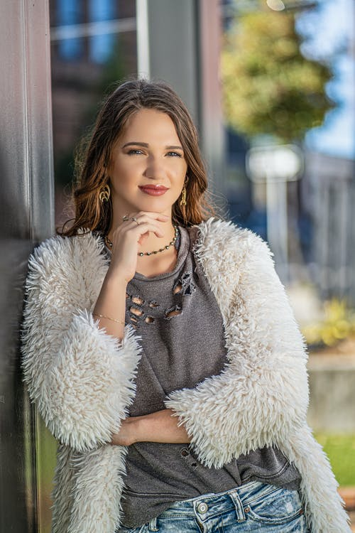 Positive female in street style clothes leaning on contemporary house wall in countryside and touching chin while looking at camera happily