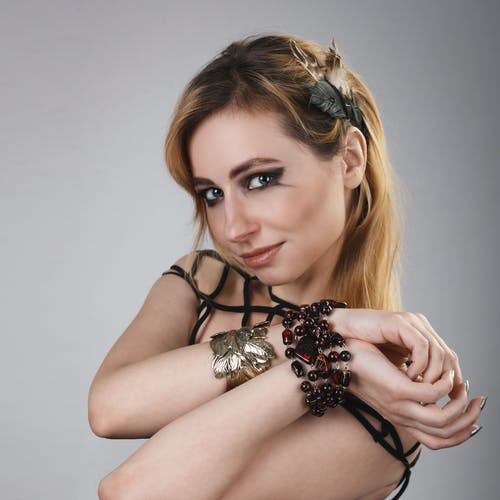 Alluring woman in bracelets with decoration in hair