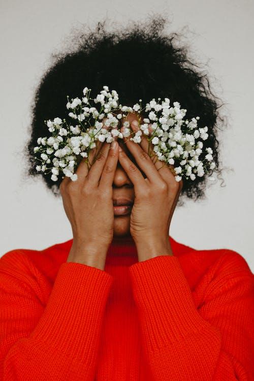Femme En Pull Rouge Tenant Des Fleurs Blanches