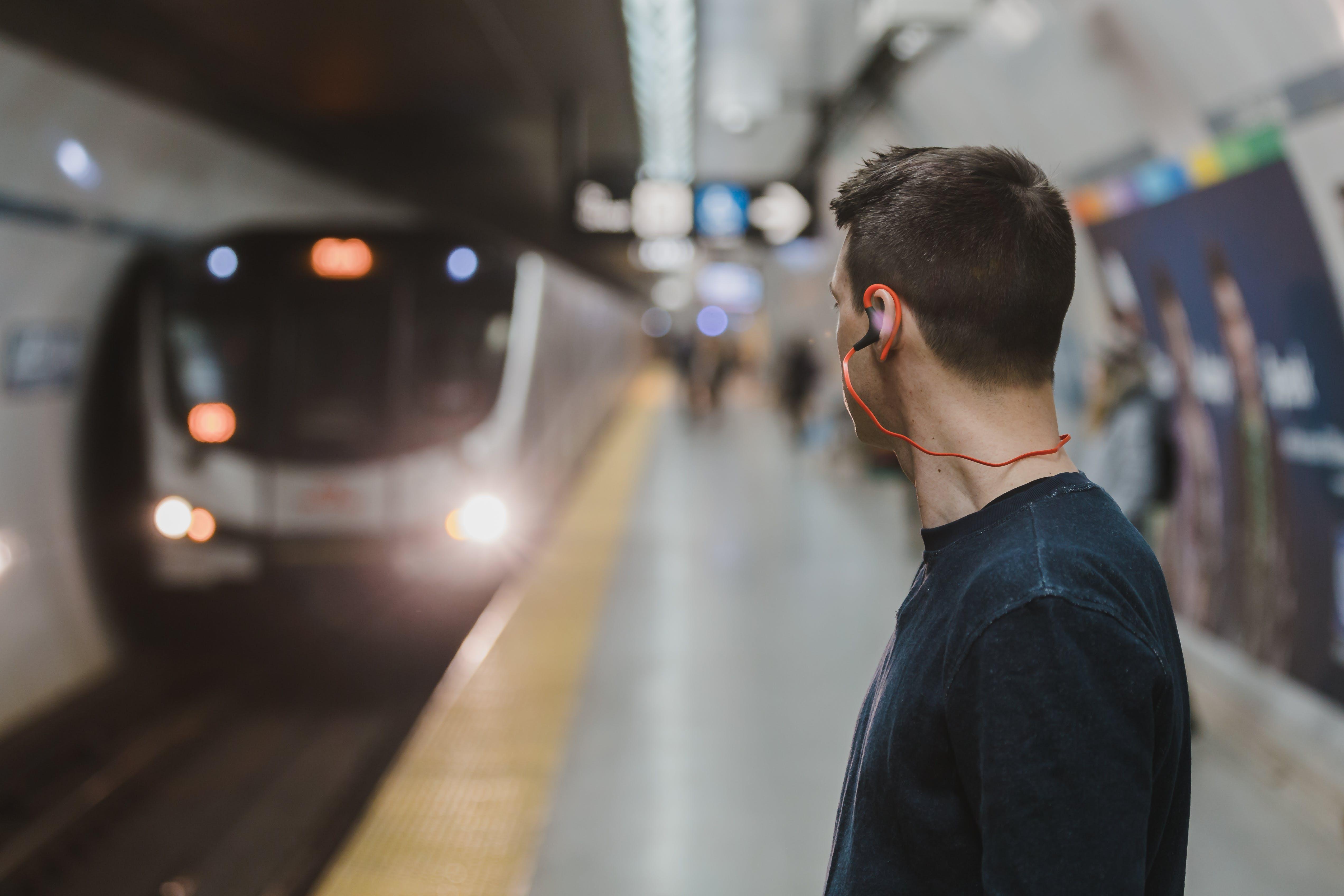 Man Using Sports Earphones on Subway Train