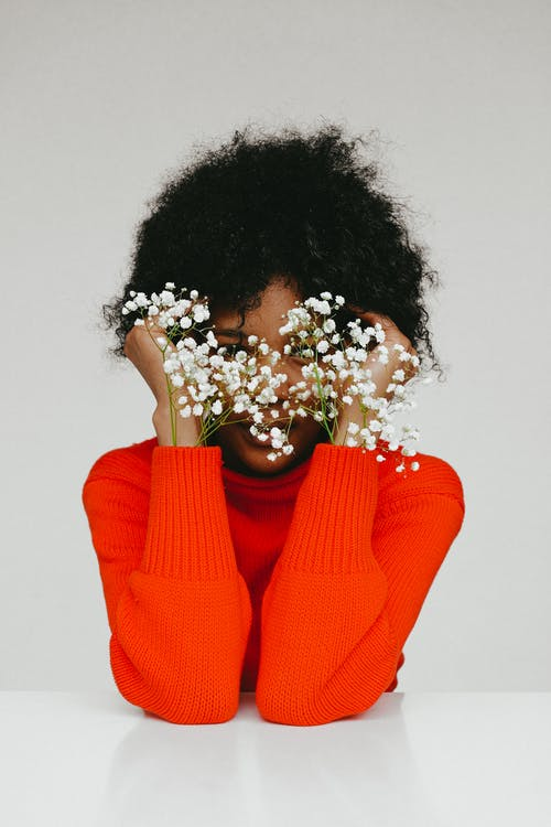 Woman in Red Sweater Holding White Flowers