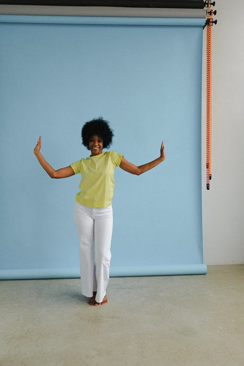 Femme En Chemise Verte Et Pantalon Blanc Debout à Côté Du Mur Bleu