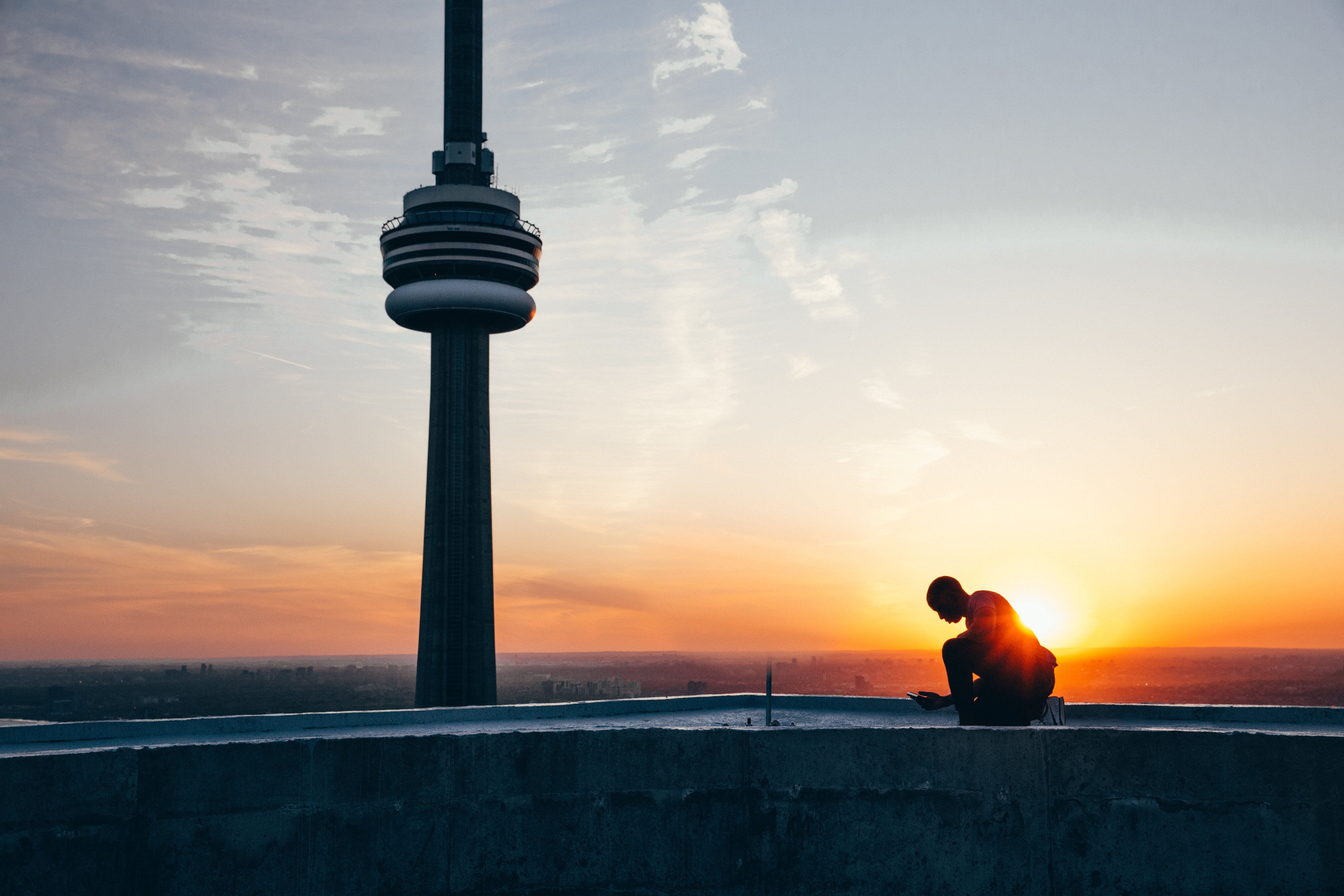 Silhouette of a Man Sitting Near Black Tower Near Body of Water during Sunset
