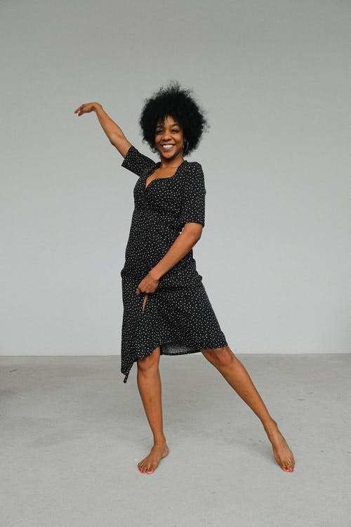 Woman in Black and White Polka Dot Dress Standing on Floor