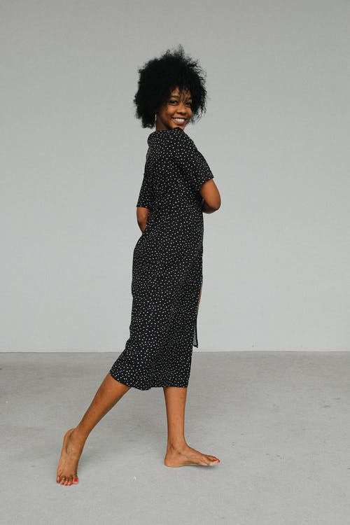 Woman in Black and White Polka Dots Dress Standing on Floor