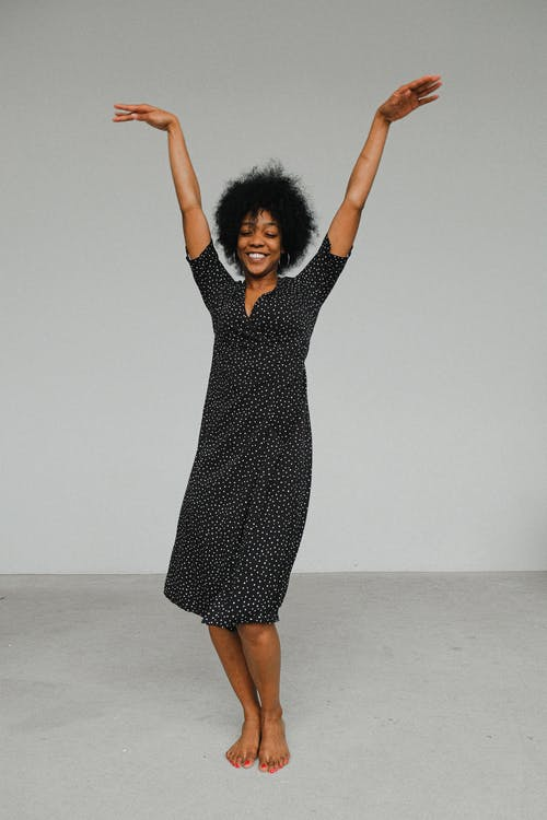 Woman in Black and White Polka Dot Dress Raising Her Hands