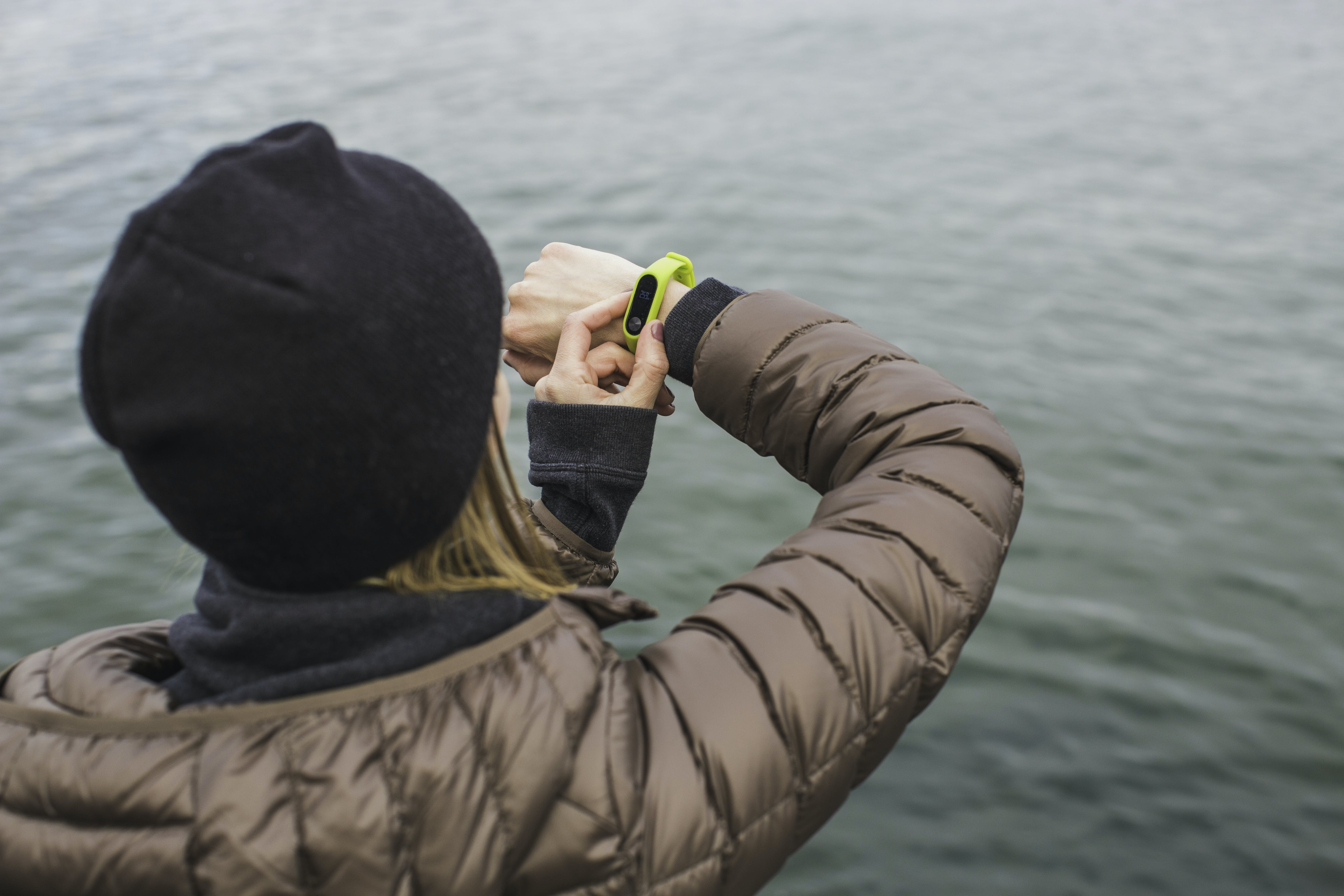 Woman Looking at Black and Yellow Activity Tracker