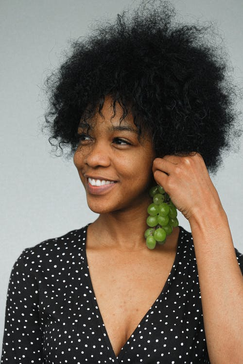 Charming black female model in polka dot dress holding bunch of grapes like earring looking away with smile