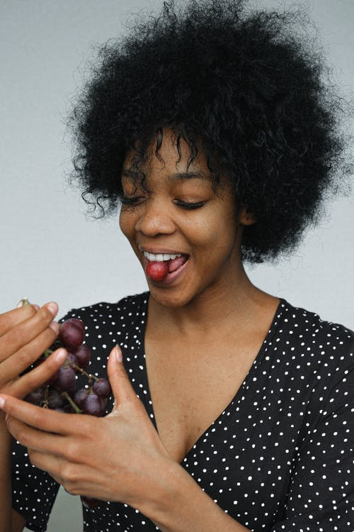 Playful black woman eating grapes in studio