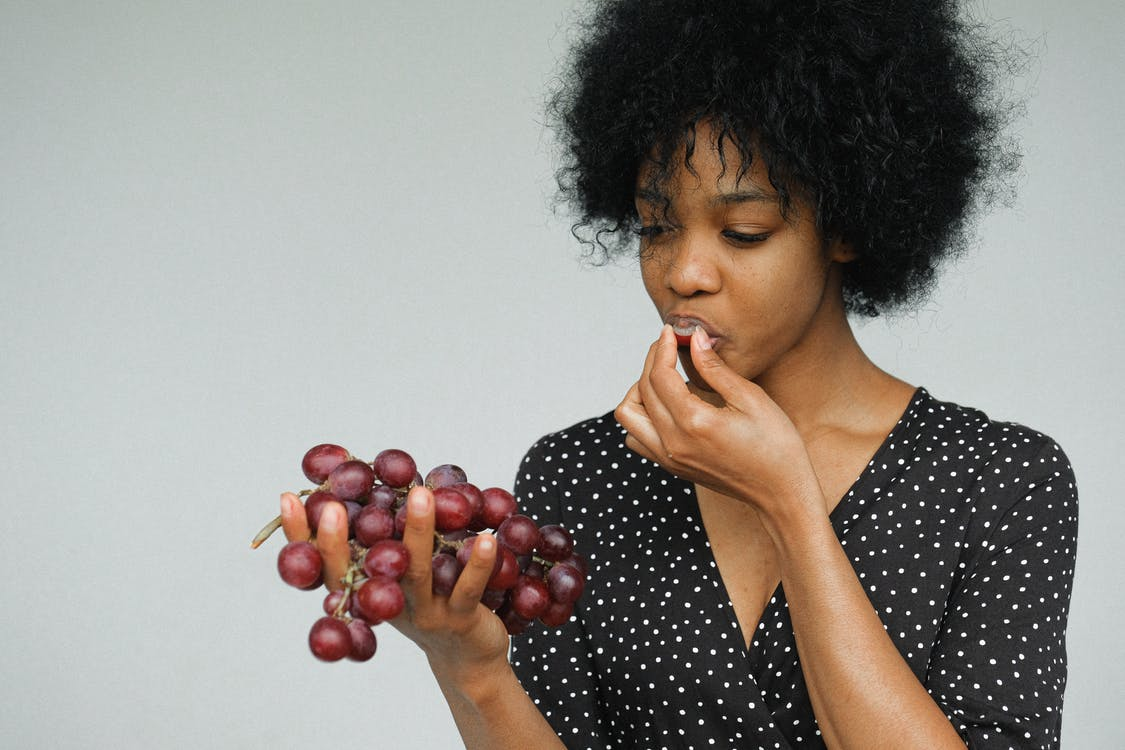 Portrait Photo of Woman in Black and White Polka Dot Dress Eating Grapes While Standing In Front of Gray Background