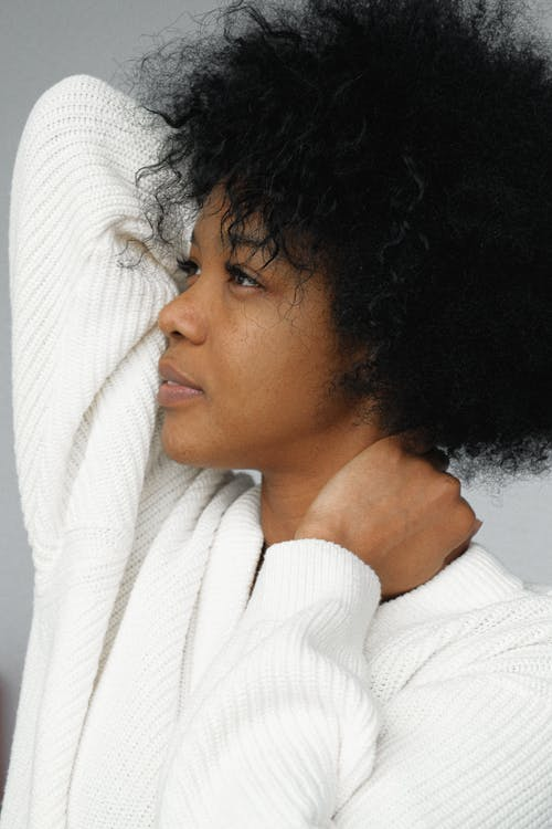 Side View Portrait Photo of Woman in White Sweater Posing In Front of Gray Background