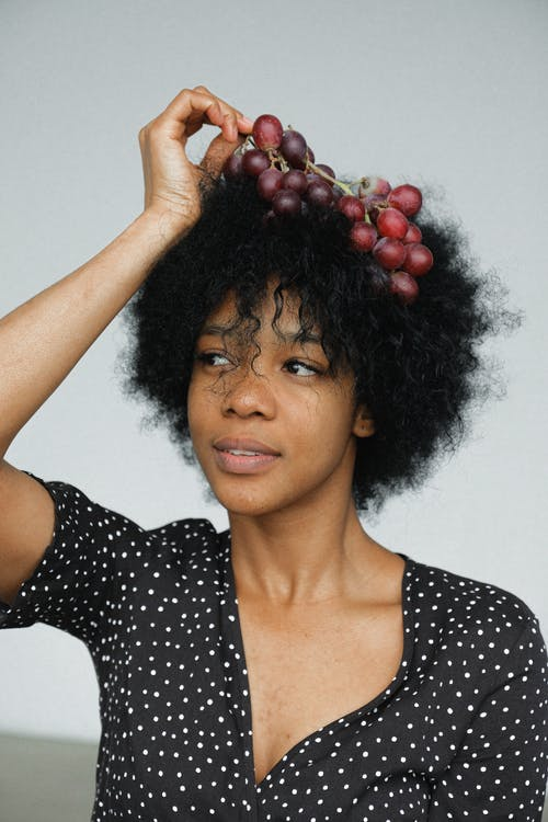 Dreamy ethnic model with grapes on head