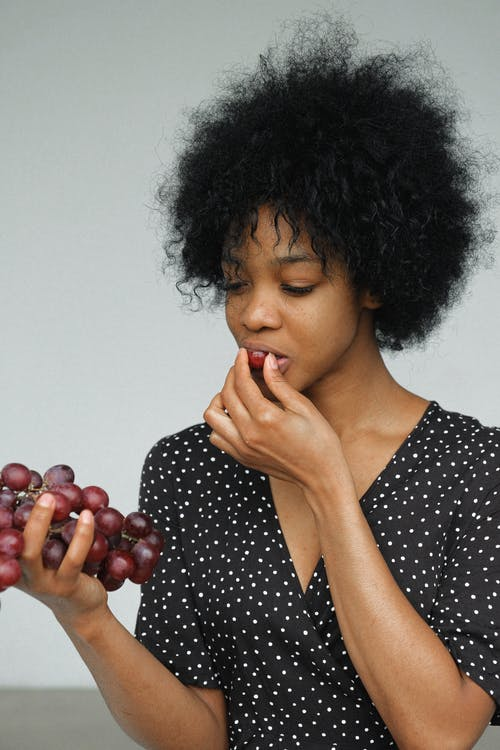 Woman in Black and White Polka Dot Shirt Holding and eating Grapes