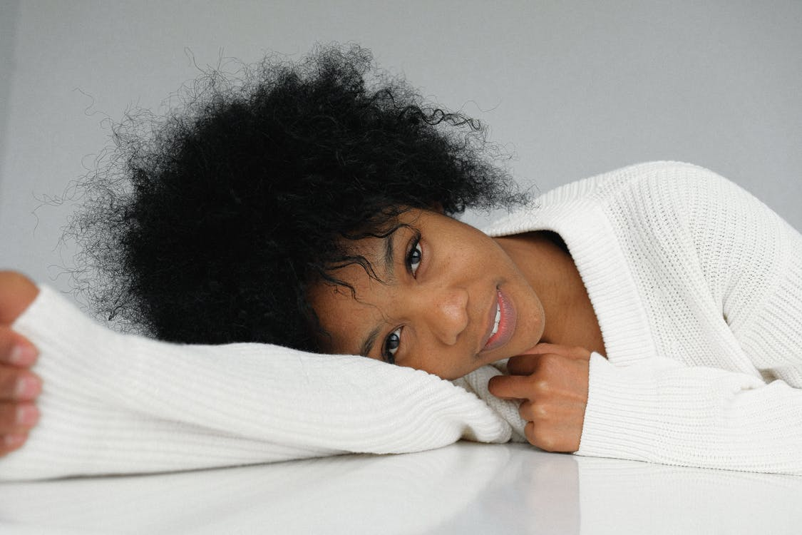 Romantic young black woman leaning on table