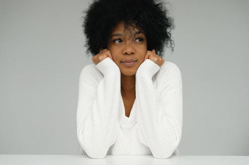 Portrait of a Woman in White Sweater Holding her Chin