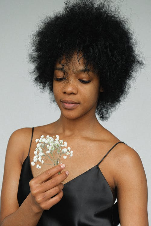 Portrait Photo of Woman in Black Spaghetti Strap Top Holding Flower