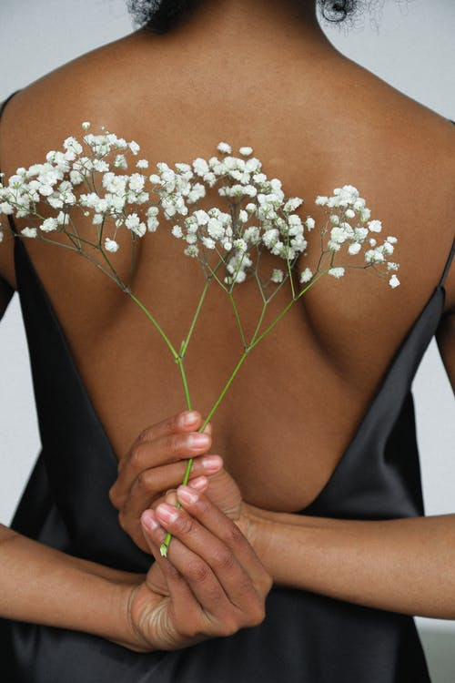 Close-up Photo of Woman in Black Night Dress Holding White Flower Behind Her Back