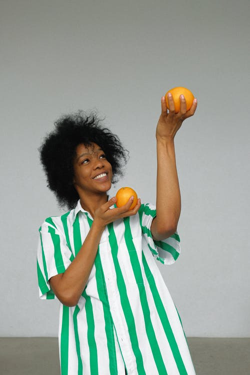 Photo of Smiling Woman in White and Green Stripe Shirt Holding up Orange Fruits