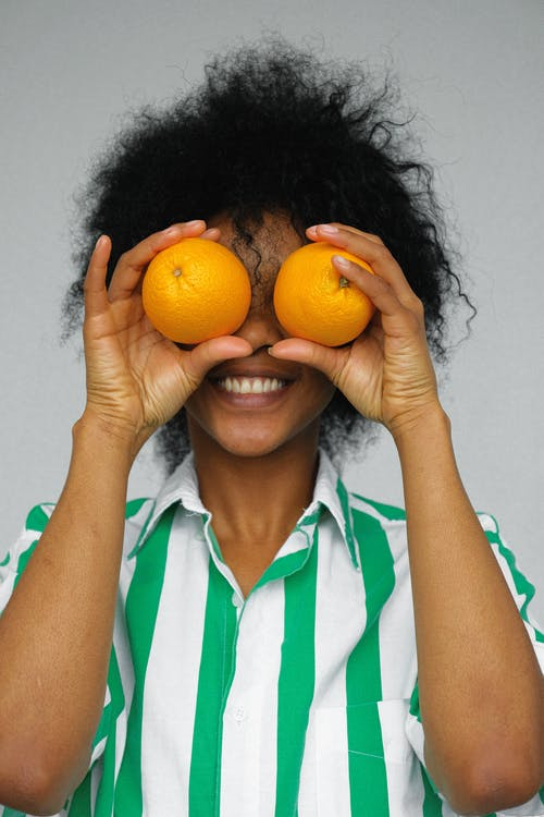 Woman in White and Green Shirt Holding Orange Fruits