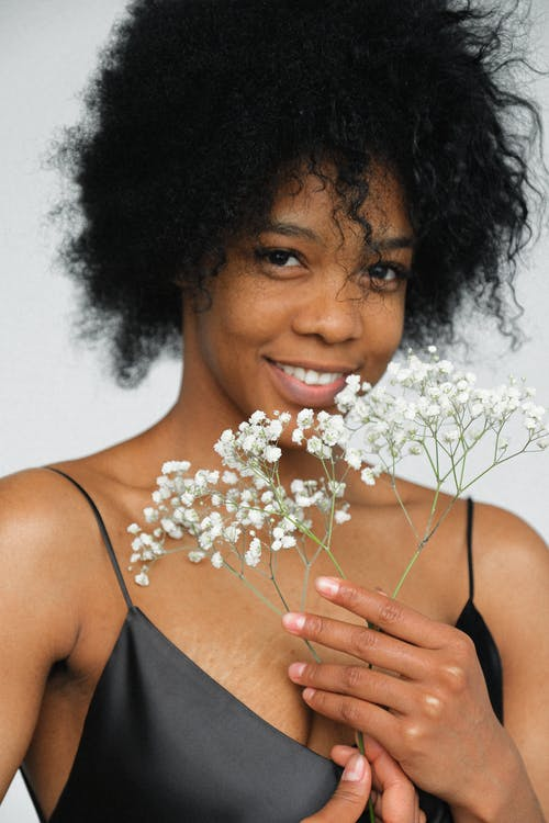 Portrait Photo of Smiling Woman in Black Spaghetti Strap Top Holding White Flower