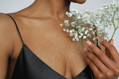Woman in Black Spaghetti Strap Top Holding White Flowers