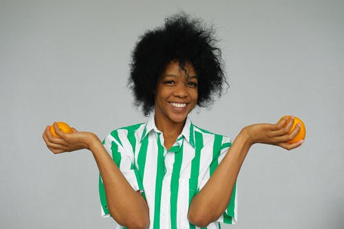 Portrait Photo of Smiling Woman in Green and White Stripe Shirt Holding Orange Fruits