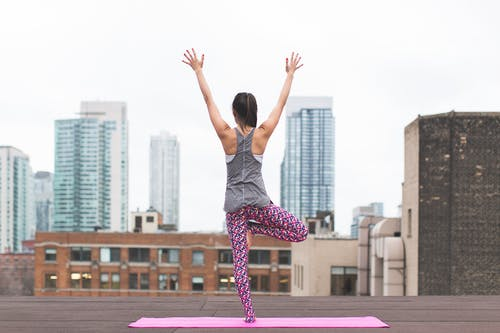 Woman Doing Yoga on Top of Building