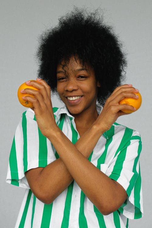 Smiling Woman in White and Blue Stripe Shirt Holding Orange Fruits