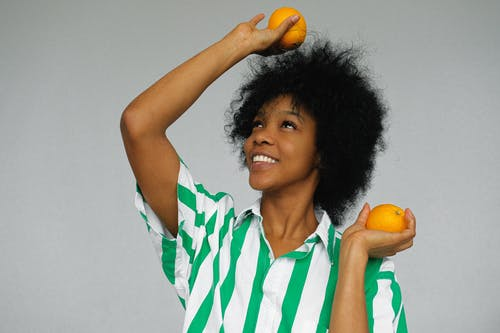 Woman in Green and White Stripe Polo Shirt Holding Orange Fruit