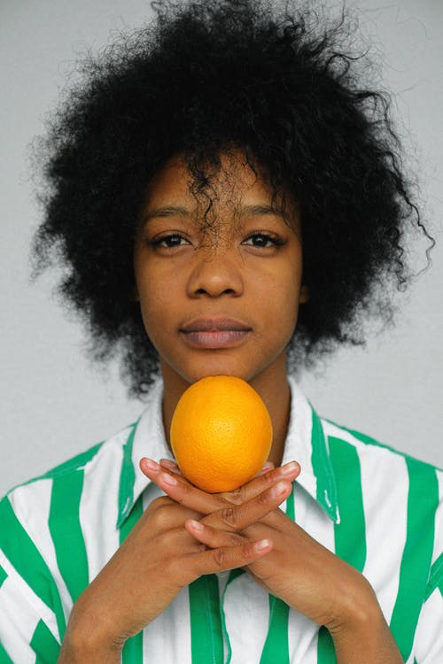Woman in Green and White Shirt Holding Orange Fruit