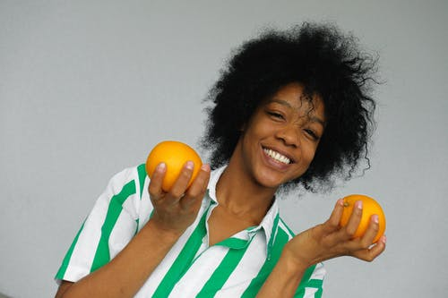 Smiling Woman in Green and White Stripe Polo Shirt Holding Orange Fruit