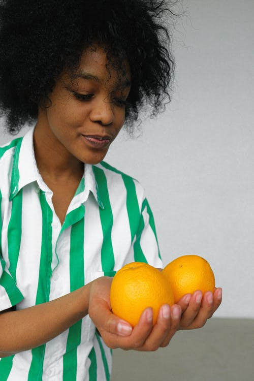 Photo of Woman in White and Green Stripe Shirt Holding Orange Fruits