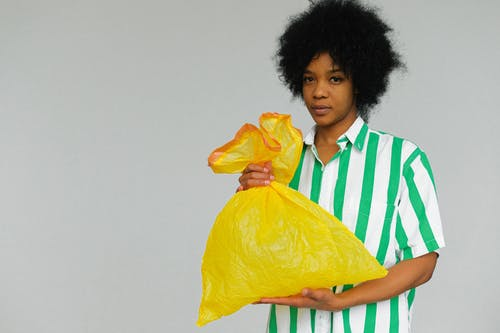 Woman in White Green Stripes Polo Shirt Holding Yellow Plastic Bag