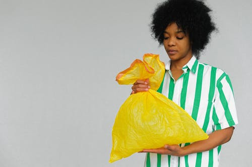 Woman Holding A Yellow Plastic Bag