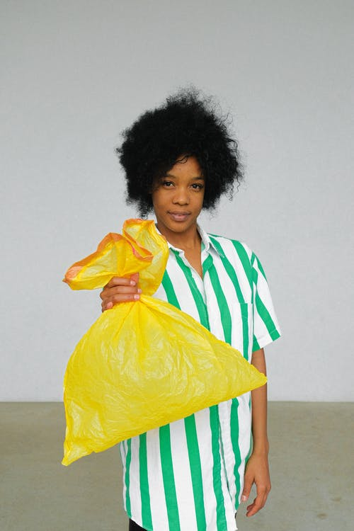 Woman Holding Yellow Plastic Bag