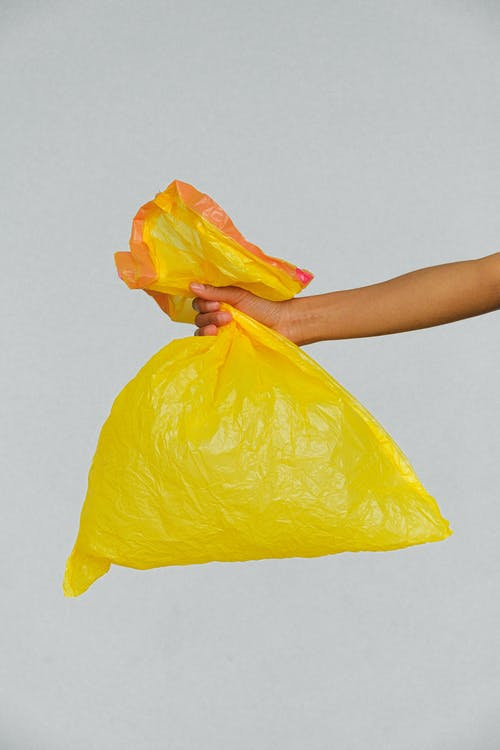 Hands Holding Yellow Plastic Bag