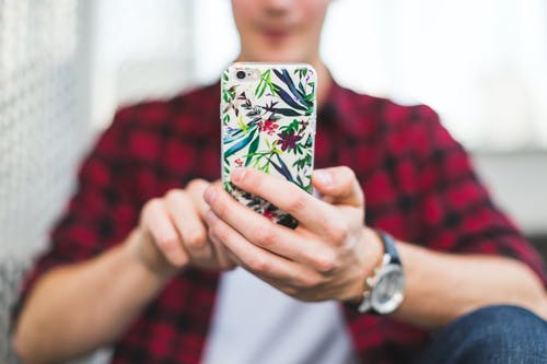 Person Holding Multicolored Floral Iphone Case