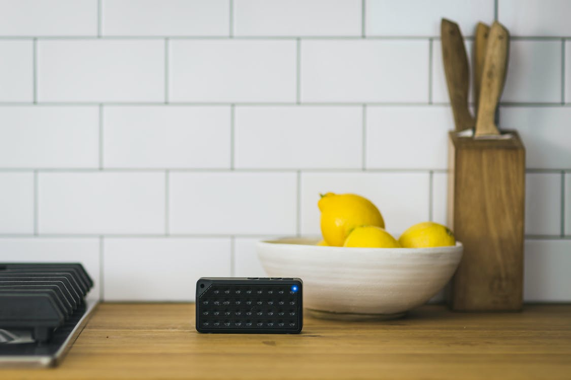 Black Portable Speaker on Top of Table Near Bowl of Lemons
