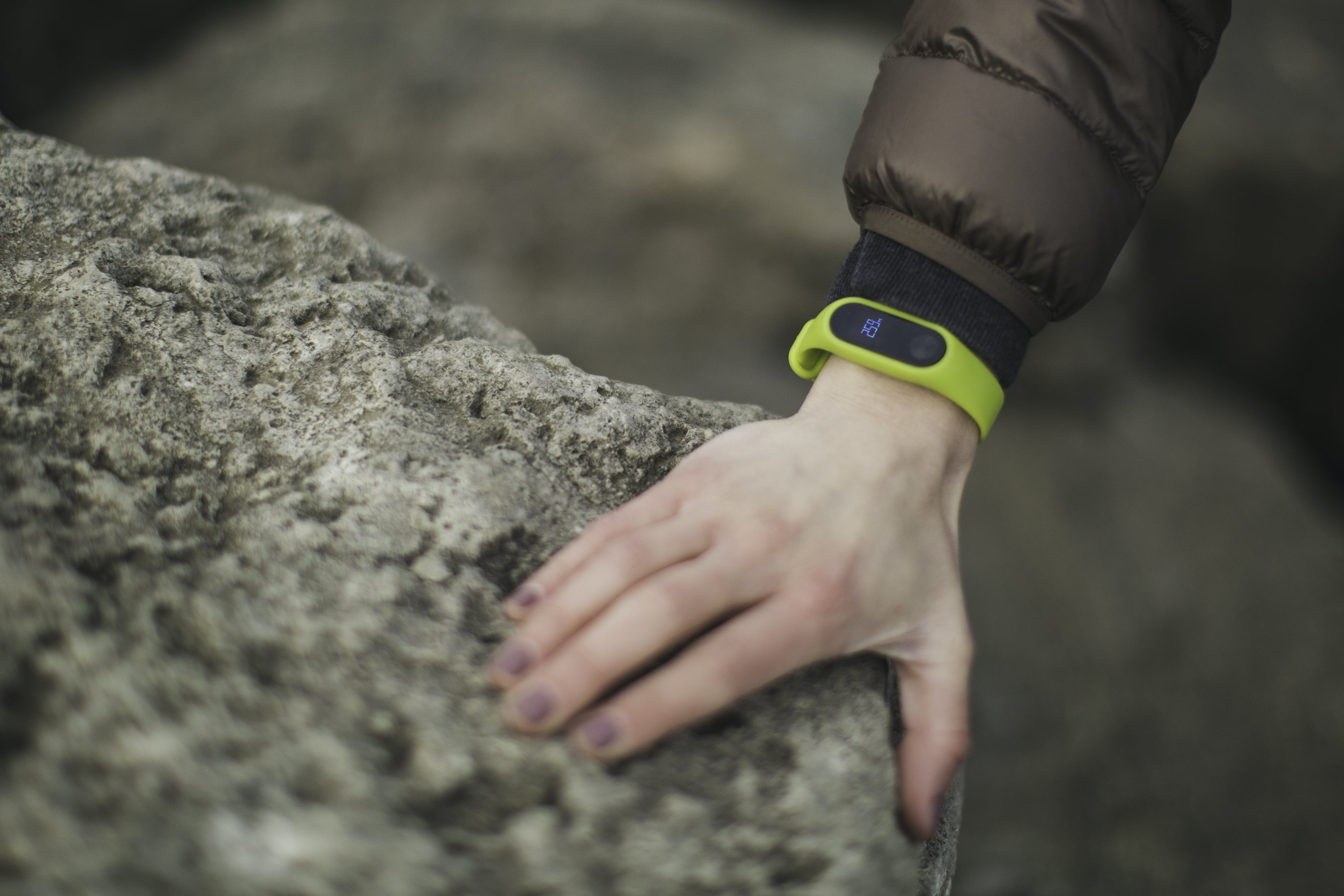 Person Wearing Yellow Fitness Band Holding Rock