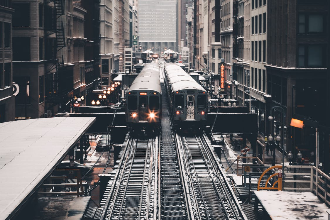 Grayscale Photography of Two Trains Beside Concrete Building