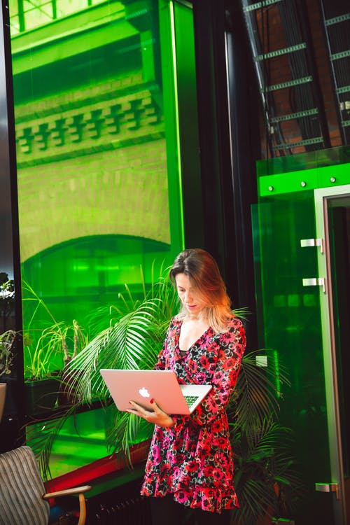 Woman in Floral Dress Using Macbook