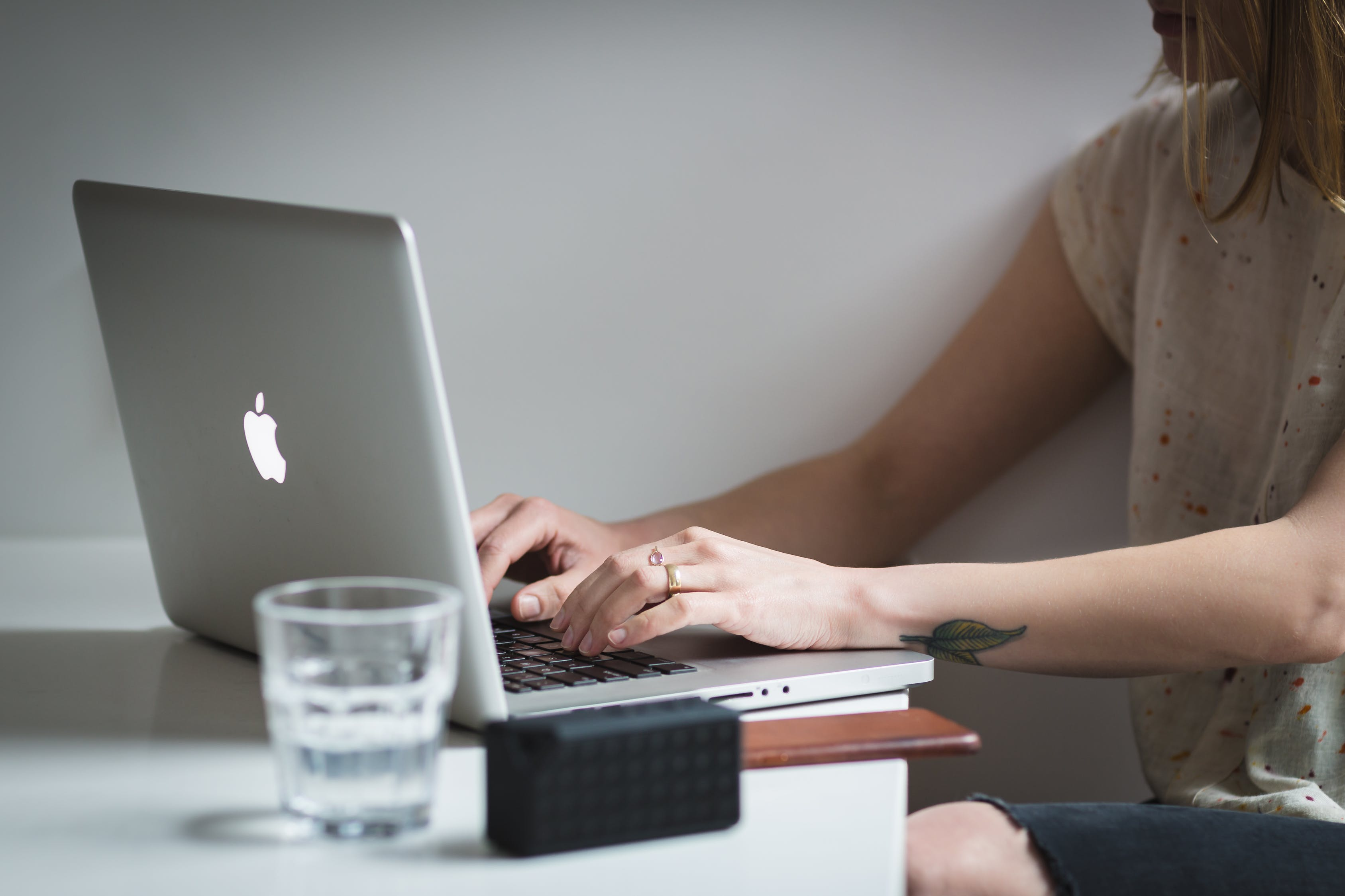Woman Using Silver Macbook Near Shot Glass on Table