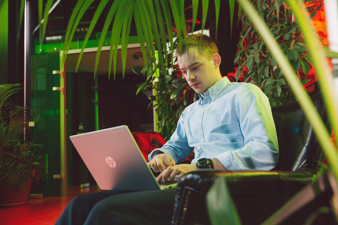 Man in Blue Dress Shirt Using Laptop