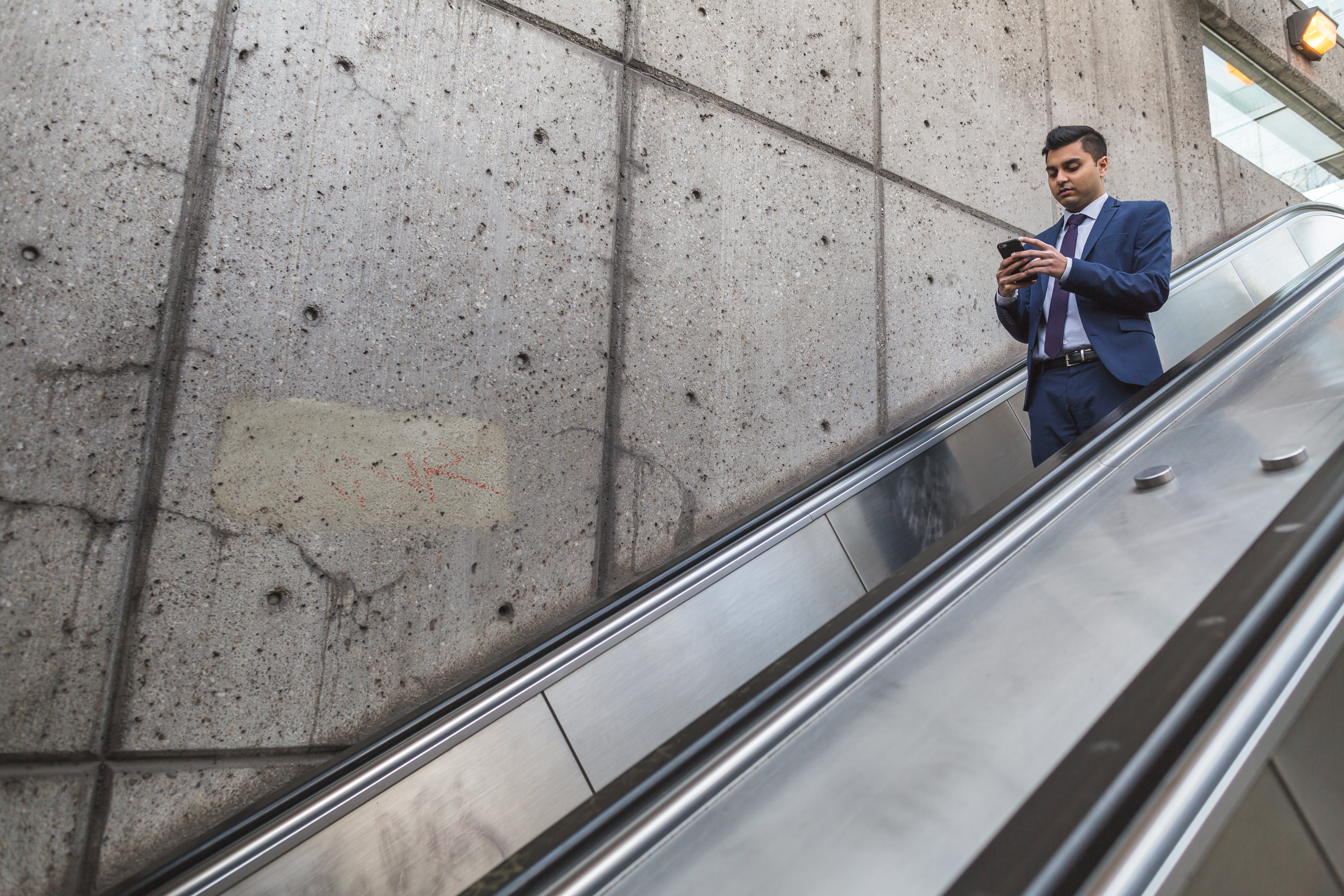 Man Wearing Blue Suit Holding Smartphone on Escalator