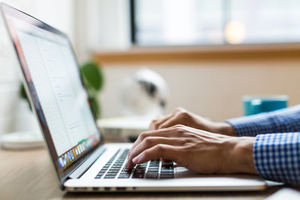 A man is typing on the laptop keyboard. | Photo: Pexels